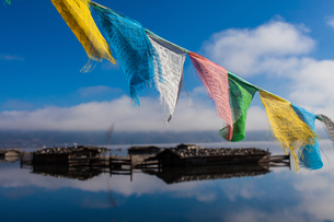 Clorful Pray Flag composite with cabins at the Napa Hai under cloudy blue skyの写真素材 [FYI02710148]