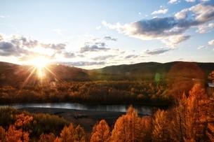 Sunlight through the mountatin range upon the forest by the river side; Town Huzhong; Da Hinggan Linの写真素材 [FYI02710166]