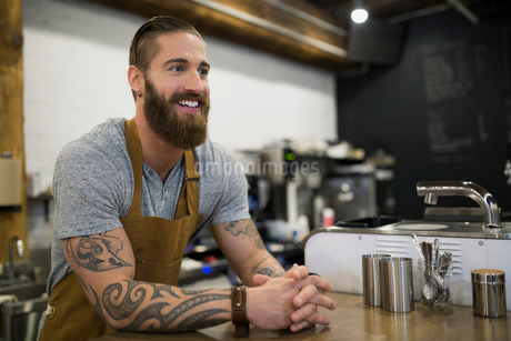 Smiling hipster barista at coffee shop counterの写真素材 [FYI02710286]