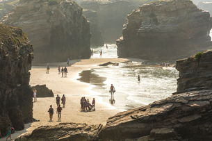 People on sandy beach surrounded by rocks.の写真素材 [FYI02710294]