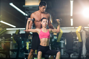 Young woman working with trainer at gymの写真素材 [FYI02710548]