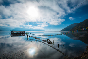 Sunlight through cloud; lake refection; cabin at the lake with pray flag line. Napa Hai Nature Reserの写真素材 [FYI02710551]