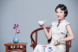 Young beautiful woman in traditional cheongsam eating porridgeの写真素材 [FYI02710812]
