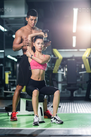 Young woman working with trainer at gymの写真素材 [FYI02710818]