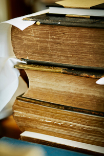 A stack of books, with yellowed worn page edges and worn bindings.の写真素材 [FYI02711190]