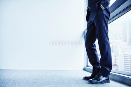 窓辺に立つ男性の足元と床の写真素材 [FYI02711447]