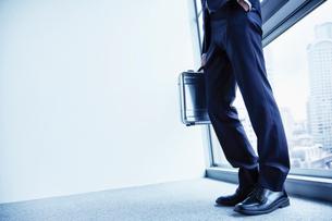 アタシュケースを持つ窓辺に立つ男性の足元と床の写真素材 [FYI02711457]