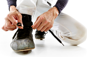 靴の紐を結ぶ野球のユニフォームを着た男性の写真素材 [FYI02711751]