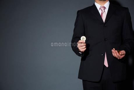 ビットコインを持ったスーツを着た男性の写真素材 [FYI02711755]