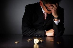 ビットコインでビジネスに失敗し頭を抱えるスーツを着た男性の写真素材 [FYI02711757]