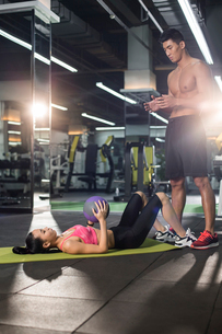 Young woman working with trainer at gymの写真素材 [FYI02712010]