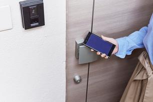 玄関のドアにスマートフォンをかざす女性の写真素材 [FYI02712259]
