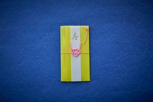 青い天板の上に置かれた黄色いご祝儀袋の写真素材 [FYI02712269]