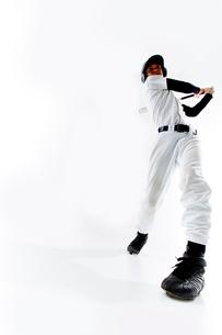 バットを振る野球のユニフォームを着た男性の写真素材 [FYI02712330]