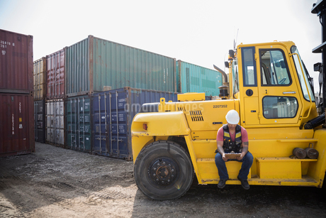 Male worker with clipboard sitting at forklift in sunny industrial container yardの写真素材 [FYI02712407]
