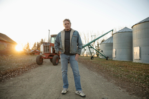 Portrait confident male farmer standing near silos on farmの写真素材 [FYI02712571]