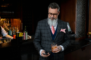 Stylish hipster businessman in suit drinking cocktail and checking smart phone in barの写真素材 [FYI02712633]