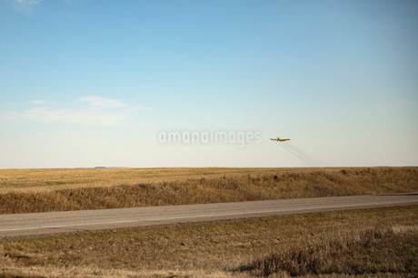 Crop duster plane flying over sunny farmの写真素材 [FYI02712635]