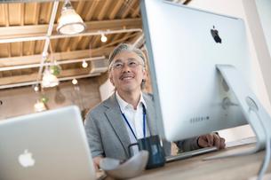 デスクで仕事をするシニアビジネスマンの写真素材 [FYI02712803]