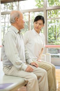 座りながら談笑するシニア男性と介護福祉士の写真素材 [FYI02712942]
