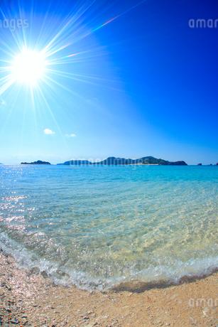 阿真ビーチの渚と嘉比島など慶良間諸島と太陽の光芒の写真素材 [FYI02716543]