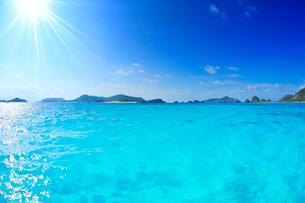トロピカル色の海と屋嘉比島など慶良間諸島と太陽の光芒の写真素材 [FYI02716692]