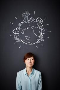 黒板に描かれた地球の絵の下で微笑む女性のイラスト素材 [FYI02717820]