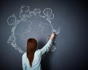 黒板に地球の絵を描く女性のイラスト素材 [FYI02717833]