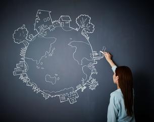 黒板に地球の絵を描く女性のイラスト素材 [FYI02718295]