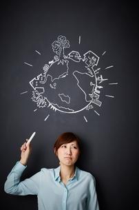 黒板に描かれた地球の絵を指す女性のイラスト素材 [FYI02718523]