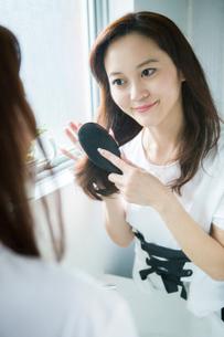 髪の毛にブラシを入れる30代女性の写真素材 [FYI02722489]