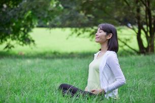 緑の中でヨガをする女性の写真素材 [FYI02722915]