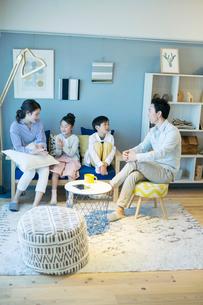 リビングで話す幸せな家族の団欒風景の写真素材 [FYI02723956]