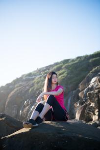 トレーニングウェアで岩の上に座っている女性の写真素材 [FYI02724080]