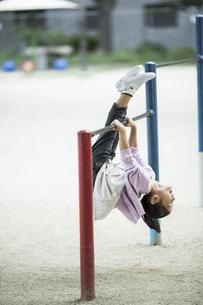鉄棒で遊ぶ女の子の写真素材 [FYI02724737]