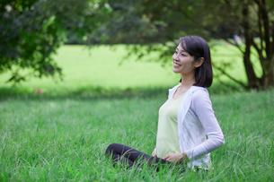 緑の中でヨガをする女性の写真素材 [FYI02724909]