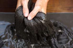 泥染をする40代女性染色家の写真素材 [FYI02730194]