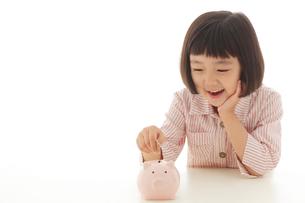 貯金箱にお金を入れるおかっぱの女の子の写真素材 [FYI02730369]