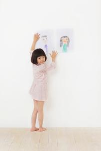 お父さんとお母さんの絵を壁に貼るおかっぱの女の子の写真素材 [FYI02730660]