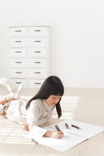 スケッチブックに色鉛筆で絵を描く女の子の写真素材 [FYI02730749]