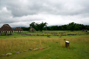 特別史跡大湯環状列石内の万座環状列石と復元された掘立柱建物と標識の写真素材 [FYI02738162]