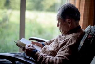 窓辺で読書をするシニア男性の写真素材 [FYI02738583]
