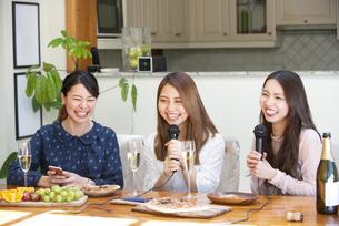 家でカラオケパーティをしている女性たちの写真素材 [FYI02739002]