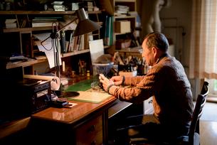 書斎でカメラを持つシニア男性の写真素材 [FYI02739153]
