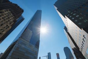 ダウンタウンビル群とワンワールドトレードセンターの間で輝く太陽の写真素材 [FYI02739188]