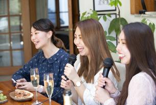 家でカラオケパーティをしている女性たちの写真素材 [FYI02739401]