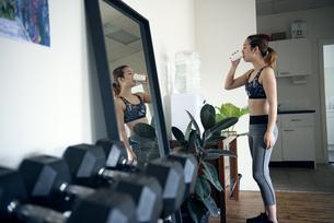 ジムでウォーターサーバーの水を飲んでいる女性の写真素材 [FYI02739726]