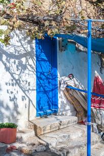 青色にペイントされた木製扉を見る田舎家の入り口風景の写真素材 [FYI02739994]