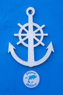真っ青な壁に取り付けられたイカリと舵輪のマークの写真素材 [FYI02740001]
