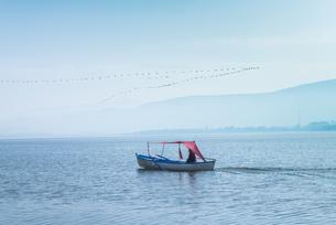 1艘のボートと真っすぐに連なって飛ぶ鳥を見るウルアバット湖風景の写真素材 [FYI02740421]